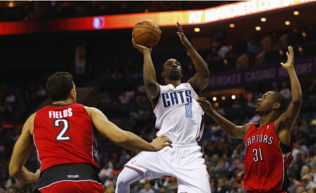 Charlotte Bobcats shooting guard Gordon shoots between Toronto Raptors small forward Fields and shooting guard Ross during the second half of their NBA basketball game in Charlotte