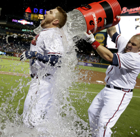 Atlanta Braves&#39; Freddie Freeman, left, is doused with water by Eric Hinske after Freeman hit a home run in the ninth inning as the Braves beat the Marlins 4-3 to clinch at least an NL wild-card playoff berth Tuesday, Sept. 25, 2012, in Atlanta. (AP Photo/David Goldman)
