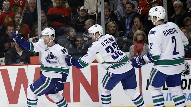 Vancouver Canucks left wing Daniel Sedin, from Sweden, left, celebrates his goal with brother Henrik Sedin (33) and Dan Hamhuis (2) during the first period of an NHL hockey game against the Chicago Blackhawks Tuesday, Feb. 19, 2013 in Chicago. (AP Photo/Charles Rex Arbogast)