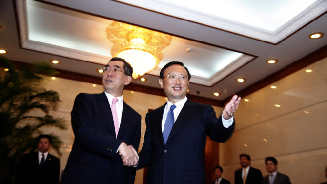 Japan's Foreign Minister Takeaki Matsumoto, left, shakes hands with Chinese Foreign Minister Yang Jiechi at the Diaoyutai state guesthouse in Beijing, China, Monday, July 4, 2011. (AP Photo/Ng Han Guan, Pool)