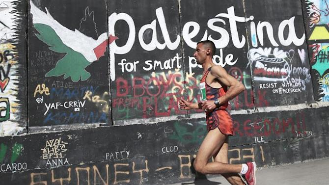 JER02. Bethlehem (---), 27/03/2015.- Photo made available 28 March 2015 of Nader Masri, a Palestinian from Beit Hanoun in the Gaza Strip, as he passes graffiti on the controversial Israeli separation barrier or wall on his way to winninghe Palestine Marathon in the West Bank town of Bethlehem, 27 March 2015. Masri was one of some 46 Palestinians form the Gaza Strip who Israeli authorities allowed to leave Gaza and participate in the marathon, and he clocked a winning tim of 2 hours 57 minutes and 14 seconds. It is the third running of the Palestine Marathon, but Masri was not allowed to exit Gaza for the previous two races. In 2008 Masri competed in the Olympics in Beijing. EFE/EPA/JIM HOLLANDER