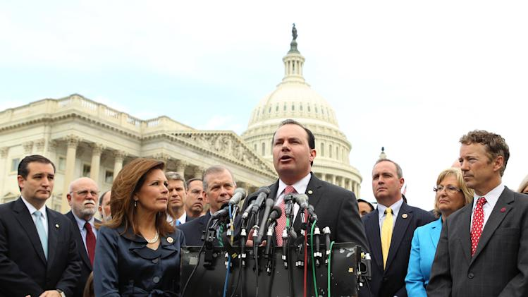 Sen. Mike Lee, R-Utah, center, accompanied by, from left, Sen. Ted Cruz, R-Texas, left, Rep. Michele Bachmann, R-Minn., chair of the Tea Party Caucus, and Sen. Rand Paul, R-Ky., right, speaks during a news conference with Tea Party leaders about the IRS targeting Tea Party groups, Thursday, May 16, 2013, on Capitol Hill in Washington. Dozens of tea party groups and other conservative organizations of the kind subjected to improper scrutiny by the Internal Revenue Service operated with small budgets and rarely displayed overt partisan activities, according to an Associated Press review of public tax filings by 93 such activist groups. A few groups built million-dollar operations and political ties that could have been legitimate grounds for IRS investigation, tax law experts said. (AP Photo/Molly Riley)