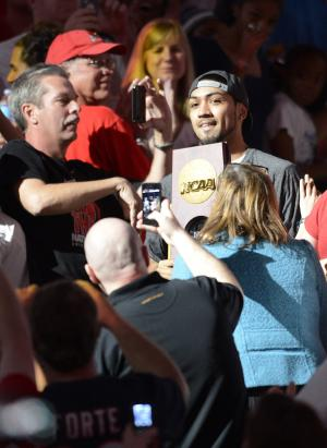 Louisville guard Peyton Siva carries the NCAA men's basketball championship trophy through the crowd at their welcome-home celebration Wednesday, April 10, 2013, in Louisville, Ky. (AP Photo/Timothy D. Easley)