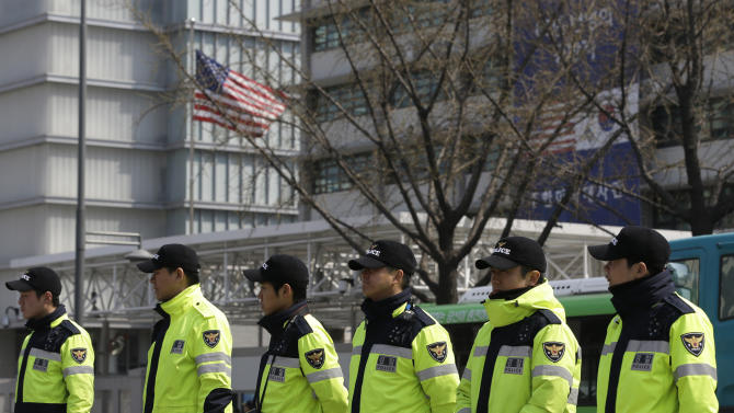 South Korean police officers stand guards during a rally denouncing the joint military exercises between South Korea and the U.S. and demanding U.S. Secretary of State John Kerry go to North Korea for peace talks, near the U.S. Embassy in Seoul, South Korea, Friday, April 12, 2013. Kerry is traveling to Asia to meet with U.S. allies and visit here on the first leg of his three-nation Asian tour. (AP Photo/Lee Jin-man)