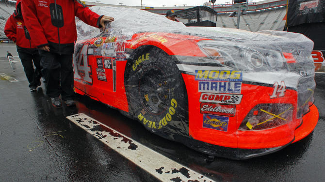 Crew members for driver Tony Stewart roll his covered car after being inspected before a NASCAR Sprint Cup Series auto race at Bristol Motor Speedway on Sunday, April 19, 2015, in Bristol, Tenn. (AP Photo/Wade Payne)