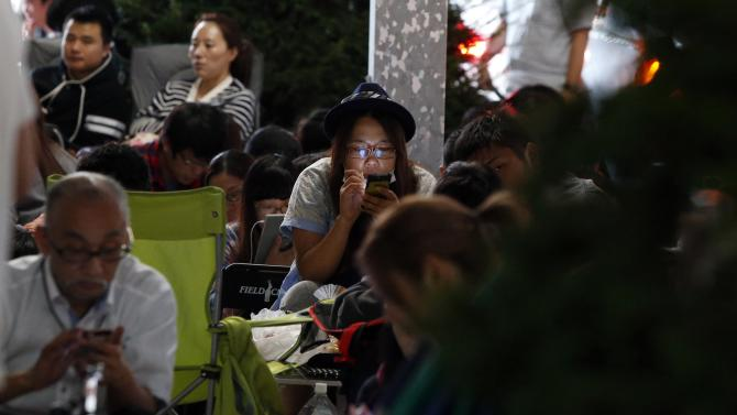 People wait for the release of Apple's new iPhone 6 and 6 Plus in front of the Apple Store at Tokyo's Ginza shopping district