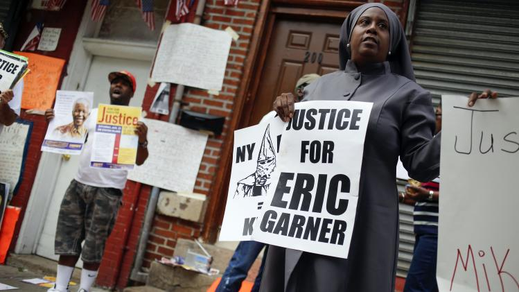 """Demonstrators stand during the """"We Will Not Go Back"""" march and rally for Eric Garner at the site where he died after being put in a choke hold by a New York City police officer, in New York"""