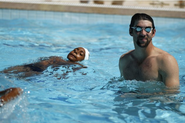 U.S. Olympic swimmer Phelps stands in a pool during a visit to the Rocinha slum complex ahead of the Laureus World Sports Awards in Rio de Janeiro
