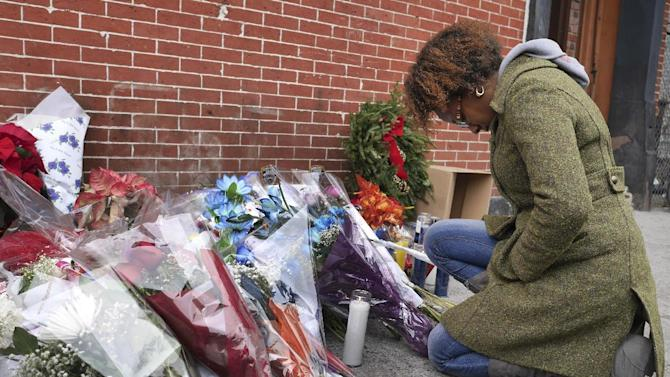 Marea Munro bows her head at an impromptu memorial near the site where two police officers were killed in the Brooklyn borough of New York, Sunday, Dec. 21, 2014. Just minutes before a wanted poster for Ismaaiyl Brinsley arrived in the NYPD's Real Time Crime Center, he ambushed two officers in their patrol car in broad daylight, fatally shooting them before killing himself inside a subway station. (AP Photo/Seth Wenig)