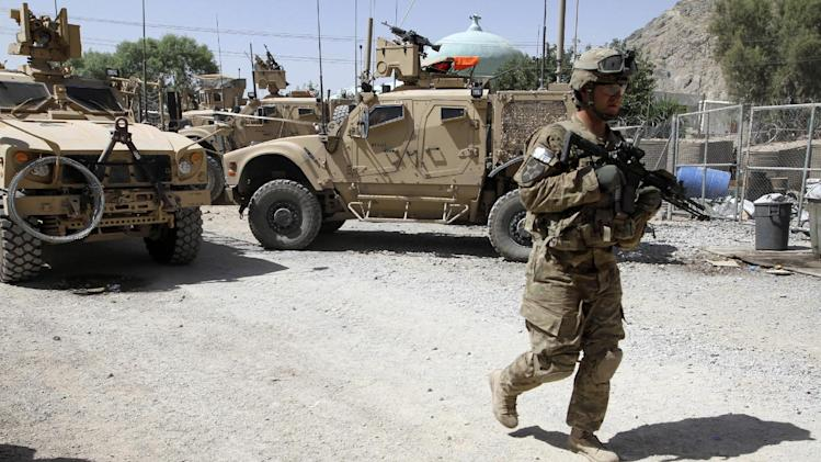 FILE - This June 19, 2012 file photo shows a US soldier, part of the NATO forces, patrols a police station in Kandahar, south of Kabul, Afghanistan. U.S. troops are still in Afghanistan, nearly 11 years after they invaded. Why? The answer boils down to one word: al-Qaida. The goal is to damage the terrorist group enough to prevent a repeat of the 9/11 attacks.  (AP Photo/Allauddin Khan, File)