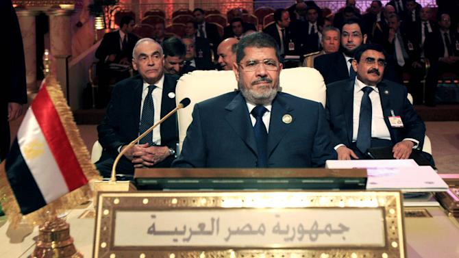 Egyptian President Mohammed Morsi, center, attends the opening session of the Arab League summit in Doha, Qatar, Tuesday, March 26, 2013. Syrian opposition representatives took the country's seat for the first time at an Arab League summit that opened in Qatar on Tuesday, a significant diplomatic boost for the forces fighting President Bashar Assad's regime. (AP Photo/Ghiath Mohamad)