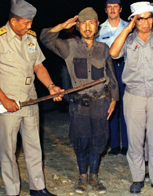 File photo shows Hiroo Onoda, a former Imperial Japanese Army intelligence officer, salutes after handing over a military sword on Lubang Island