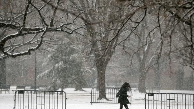 A woman runs through the snow in Lafayette Park near the White House in Washington