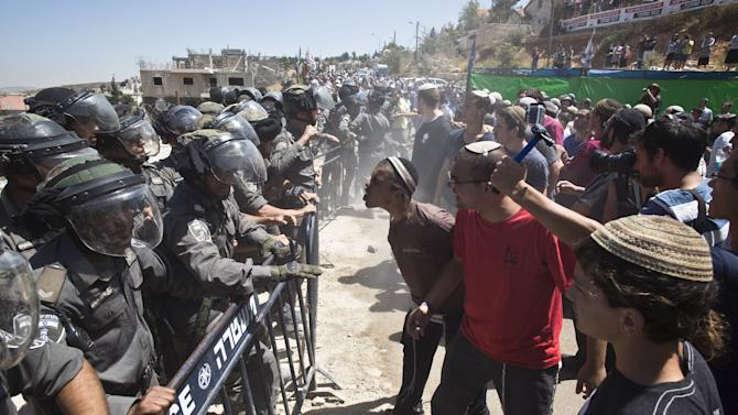 Israeli paramilitary police stand in front of Jewish settlers protesting the demolition of two partially-built dwellings in the West Bank Jewish settlement of Beit El near Ramallah