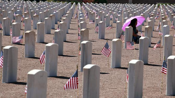A woman shades herself from the sun while sitting in front of a grave during Memorial Day celebrations at Fort Bliss in El Paso