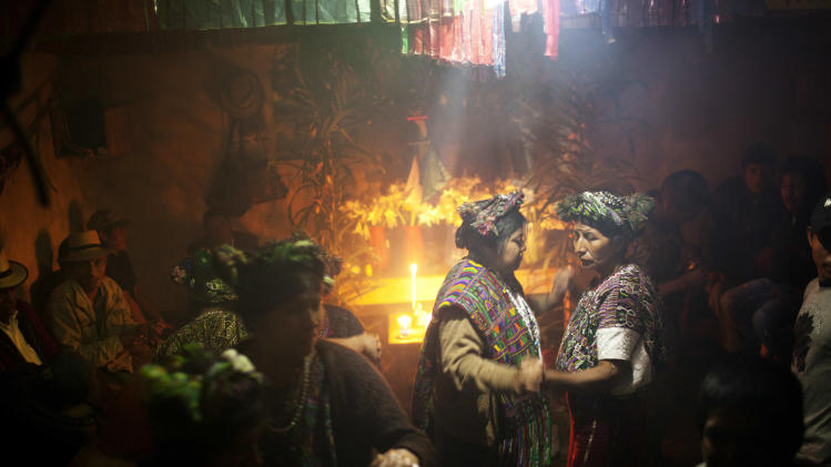 """In this May 23, 2013 photo, Ixil Mayan women perform a traditional dance called """"Sarabanda"""" in Nebaj, Guatemala. Forgotten by the state for centuries, the Ixil have recently come under the spotlight after a court found former dictator Efrain Rios Montt guilty of genocide for the ruthless policies used during his 17-month-long regime against the Ixil. The sentence was later overturned by a higher court. Bereft of basic services like education, health, access to clean water and sanitation, the Ixil people carry on as they have done for generations. (AP Photo/Rodrigo Abd)"""