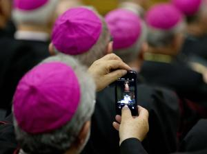 A bishop photographs Pope Francis as he delivers his …