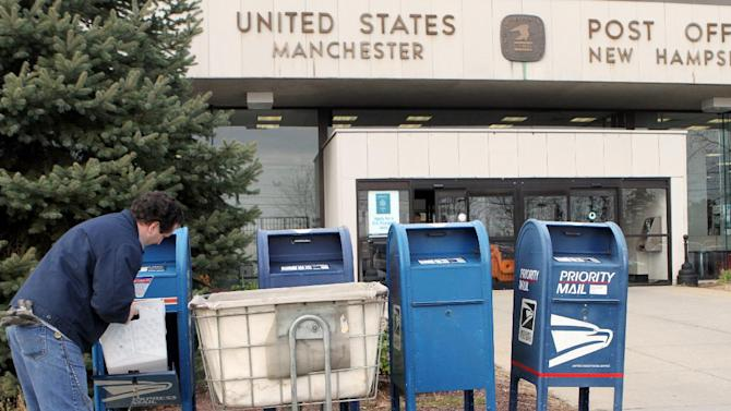 A postal worker collects mail in front of the Post Office, Monday, Dec. 5, 2011 in Manchester, N.H. The office is one of many that could be closed when he estimated $3 billion in reductions takes effect.  (AP Photo/Jim Cole)
