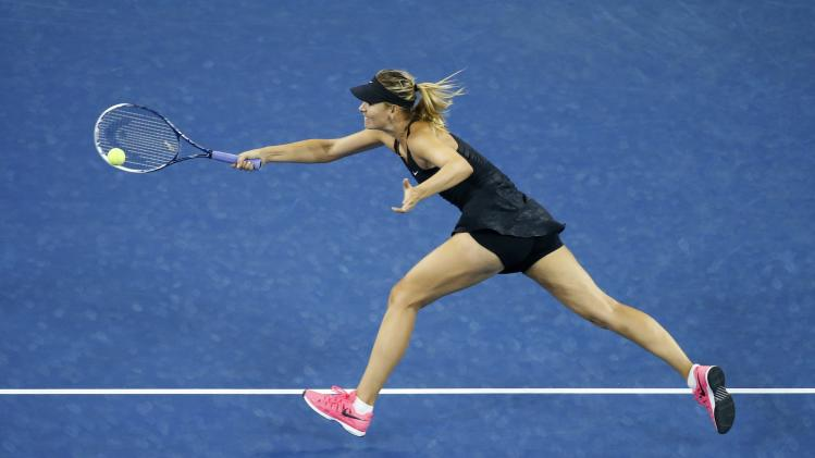Maria Sharapova of Russia returns a shot to Sabine Lisicki of Germany in their women's singles match at the 2014 U.S. Open tennis tournament in New York