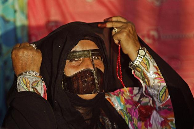 In this Dec. 24, 2010 photo, an Emirati woman in traditional dress covers a colorful gown with an abaya during the Al-Dhafra festival close to Madinat Zayed, about 150 kilometers southwest of Abu Dhab
