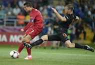 Portuguese forward Cristiano Ronaldo (L) kicks the ball past Dutch defender Ron Vlaar during the Euro 2012 football championships match Portugal vs. Netherlands on June 17, 2012 at the Metalist stadium in Kharkiv.  AFP PHOTO / FILIPPO MONTEFORTE