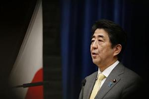 Japan's Prime Minister Shinzo Abe speaks next to the Japanese national flag, attached with a black ribbon, during a news conference in Tokyo