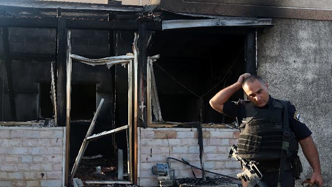 A member of the Israeli security forces inspects a Palestinian house that was set on fire in the West Bank village of Duma on July 31, 2015