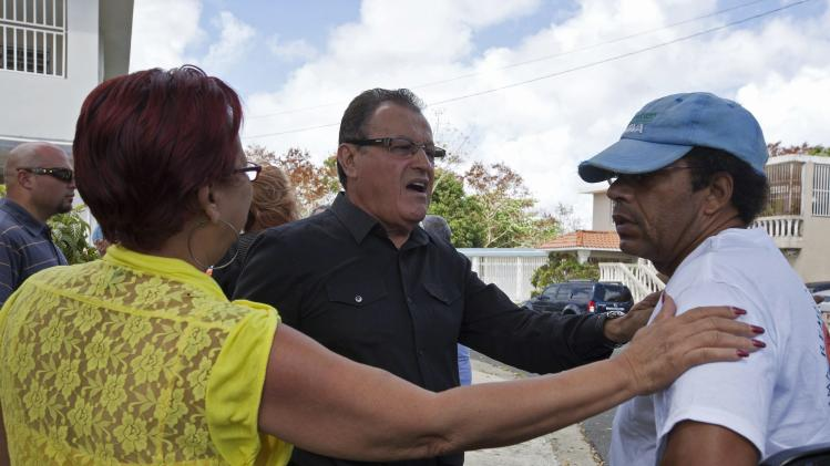 "Tropical and salsa singer Miranda comforts Richy, one of the five sons of singer Jose ""Cheo"" Feliciano, in front of Cheo's residence in San Juan"