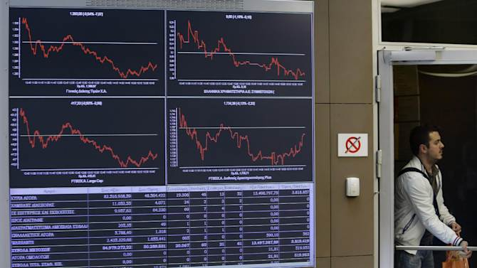 An employee of the Stock Exchange opens the door next to a display showing stock price movements in Athens, Wednesday, April 9, 2014. Greece confirmed Wednesday that it is returning to international bond markets for the first time in four years amid growing signs of confidence in the country that triggered the European debt crisis. (AP Photo/Thanassis Stavrakis)
