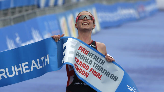 Non Stanford of Britain celebrates her race win and the world series championship as she crosses the finishing line of the elite women race during the World Triathlon Grand Final in Hyde Park, London, Saturday, Sept. 14, 2013. (AP Photo/Sang Tan)