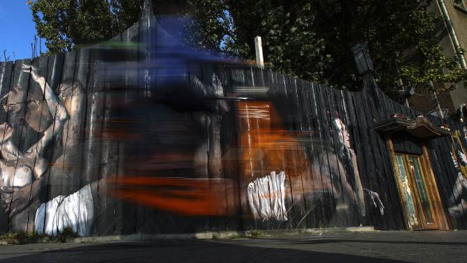 "A cyclist passes paintings of Italian street artist ""Gomez"" on a wooden fence in Berlin"