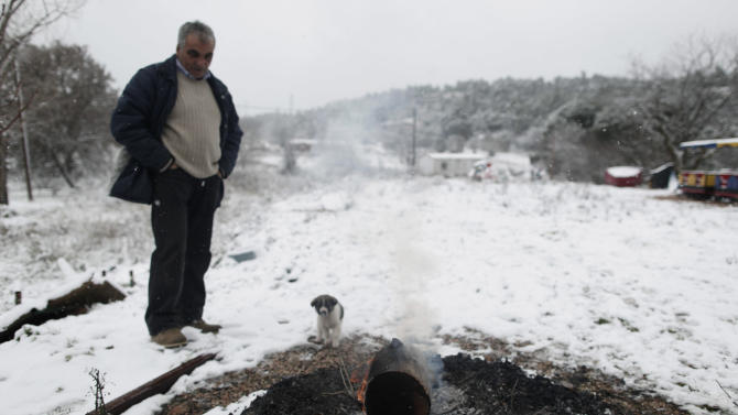 In this picture taken onTuesday, Jan, 8, 2013, fairground owner Yannis Kasternopoulos warms himself over an open fire as snow blankets his grounds in Stamata, on the northern fringes of Athens. A steep increase in heating costs has forced many in crisis-hit Greece to switch from heating oil to wood-burning for warmth. But there's a catch. Illegal loggers are slashing through forests devastated by years of summer wildfires, air pollution from wood smoke is choking the country's main cities and there has been an increase in blazes caused by carelessly attended woodstoves.(AP Photo/Petros Giannakouris)