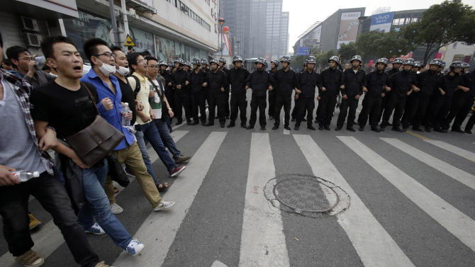 Protesters march past Chinese policemen in Zhejiang province's Ningbo city, protesting the proposed expansion of a petrochemical factory Sunday, Oct. 28, 2012. Thousands of people in the eastern Chinese city clashed with police Saturday while protesting the proposed expansion of the factory that they say would spew pollution and damage public health, townspeople said. (AP Photo/Ng Han Guan)