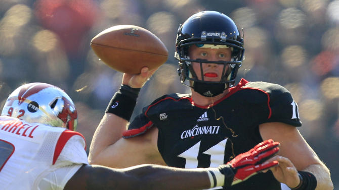 Cincinnati quarterback Brendon Kay (11) passes under pressure from Rutgers defensive lineman Jamil Merrell (92) in the first half of an NCAA college football game, Saturday, Nov. 17, 2012, in Cincinnati. (AP Photo/Al Behrman)