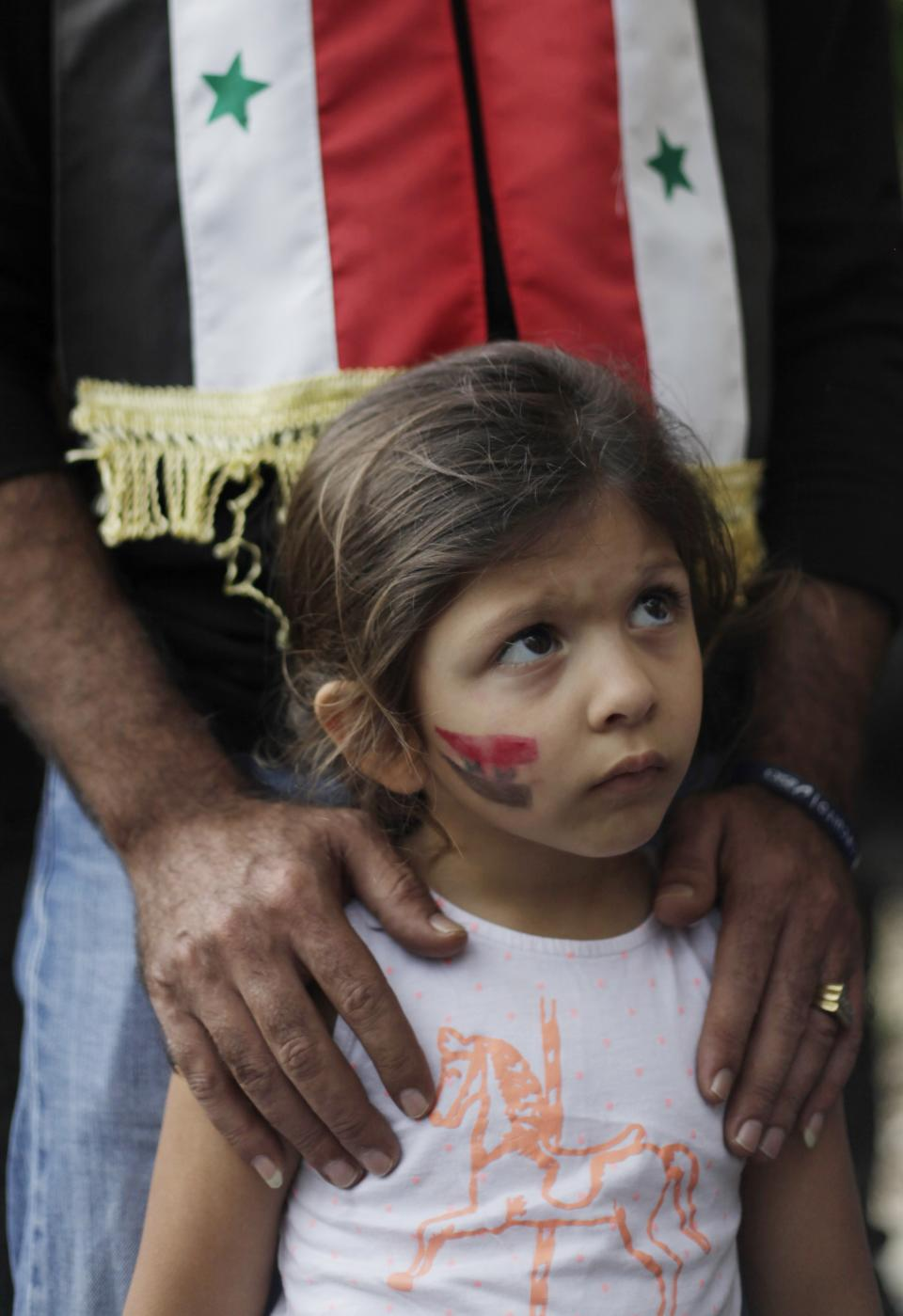 A girl with the Syrian flag painted on her cheek attends a demonstration by adults protesting any military action in Syria by the U.S., outside the U.S. embassy in Caracas, Venezuela, Monday, Sept. 2, 2013. (AP Photo/Ariana Cubillos)