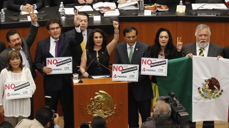 Senators of the PRD hold placards and a Mexican flag while interrupting a debate on an energy reform bill at the Senate in Mexico City