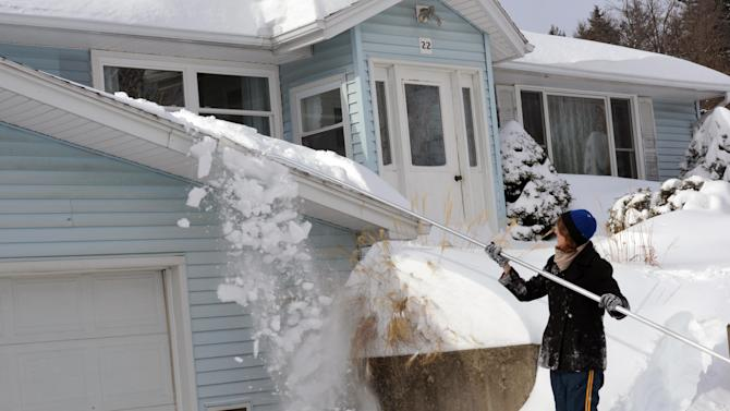 Jackie Humphreys uses a snow rake to lessen the load the roof of her home, Saturday, Feb. 9, 2013 in Holyoke, Mass. A howling storm across the Northeast left the New York-to-Boston corridor shrouded in 1 to 3 feet of snow Saturday, stranding motorists on highways overnight and piling up drifts so high that some homeowners couldn't get their doors open. More than 650,000 homes and businesses were left without electricity. (AP Photo/The Republican, John Suchocki)