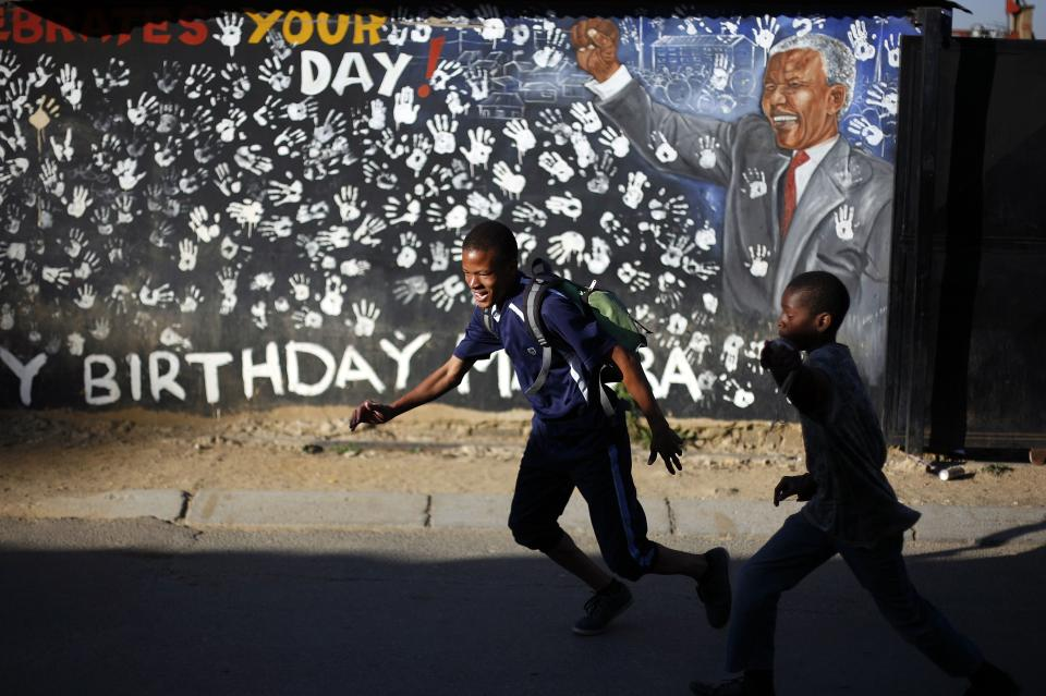 School pupils walk in front of a year old mural outside former South African President Nelson Mandela's former Alexandra township residence in Johannesburg, South Africa, Thursday June 13, 2013. Nelson Mandela remained hospitalized for the sixth day with an occurring lung infection. The latest government report says that he remains in a serious but stable condition. (AP Photo/Jerome Delay)