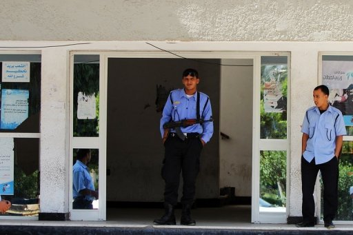 Libyan security men stand at the entrance of a police station in September 2012 in Benghazi, Libya. A car exploded outside a police station in Libya's second city of Benghazi on Sunday, causing damage to the building and lightly wounding three policemen, an AFP photographer and witnesses said