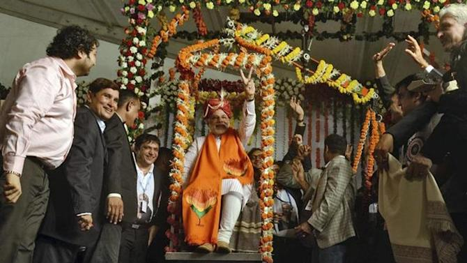 Hindu nationalist Narendra Modi, prime ministerial candidate for India's main opposition Bharatiya Janata Party (BJP), sits on a weighing scale balanced with silver during the inauguration of the Mumbai Diamond Merchant Association's Diamond Hall in Mumbai September 30, 2013. REUTERS/Stringer