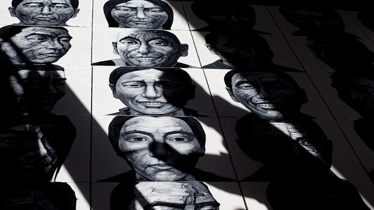 In this photo taken on Tuesday, Dec. 25, 2012, Beijing-based artist Liu Yi casts his shadow on his painting of portraits of Tibetans who have self-immolated over the past three years as he works at his studio in Songzhuang art village in Tongzhou, on the outskirt of Beijing. Liu is working on a series of black-and-white portraits he knows will never be shown in a Chinese gallery. His varied subjects - men and women, young and old, smiling and pensive - have one thing in common: They are Tibetans who have set themselves on fire to protest repressive Chinese rule. (AP Photo/Andy Wong)