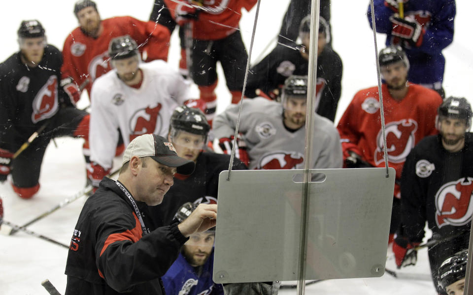 Members of the New Jersey Devils listen as head coach Peter DeBoer, left foreground, talks during practice in preparation for Wedensday's Game 1 of the NHL hockey Stanley Cup Final series against the Los Angeles Kings, Tuesday, May 29, 2012, in Newark, N.J. (AP Photo/Julio Cortez)