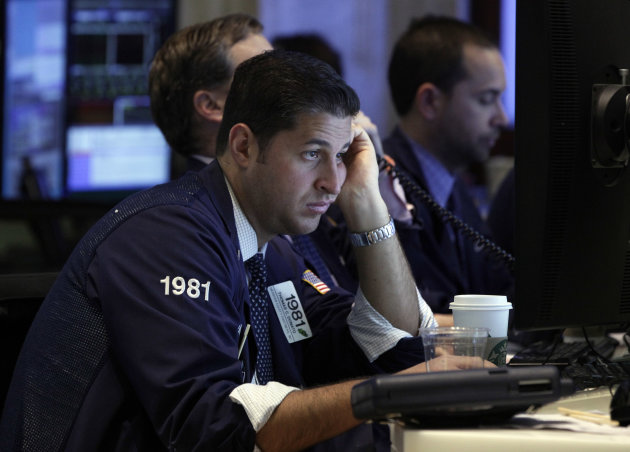 Trader Thomas Donato looks at a screen as he works on the floor of the New York Stock Exchange Tuesday, Oct. 23, 2012. Stocks are falling sharply at the opening of trading on Wall Street after 3M and DuPont slashed their earnings forecasts. (AP Photo/Richard Drew)