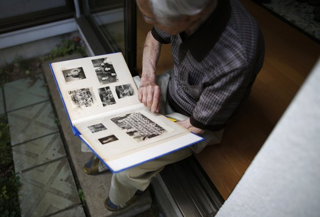 Former Japanese army medic Matsumoto, 91, looks at 1940s photos of himself during an interview with Reuters in Sagamihara