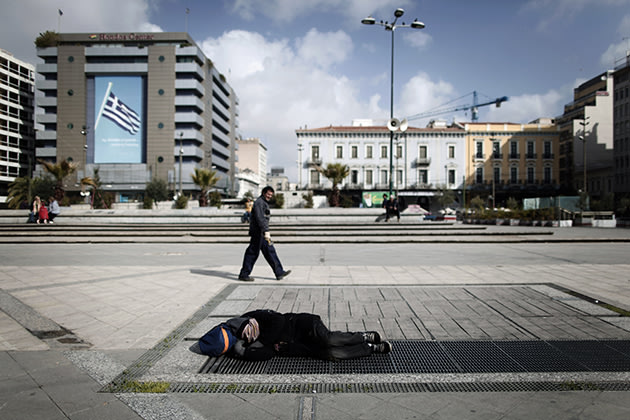 A pedestrian walks by as a homeless man sleeps on a metro air vent in Athens. (AP Photo/Petros Giannakouris)