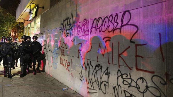 Police officers shadows are cast onto graffiti on the wall of a Subway during the second night of demonstrations in Oakland