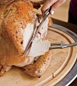 5. Hold the turkey steady with the carving fork and slice the breast. Each slice will fall when the knife reaches the cut from Step 4.