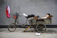 A peddler rests on his trishaw in Beijing. China's industrial output growth weakened in August to its slowest pace in more than three years, official figures showed, confirming a deepening slowdown in the world's second-biggest economy