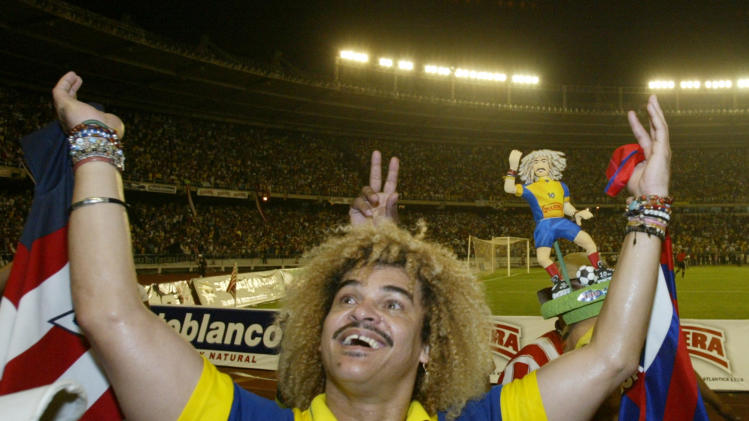"FILE- In this Feb. 1, 2004, file photo, Carlos ""El Pibe"" Valderrama waves at the end of an exhibition game to formalize his retirement from professional soccer in the coastal city of Baranquilla, in northern Colombia. ""El Pibe"" lived up to his candid nature by declaring that the teams he captained in the 1990's would have advanced further in World Cup play had the players been freed from chastity. (AP Photo/Ricardo Mazalan, File)"