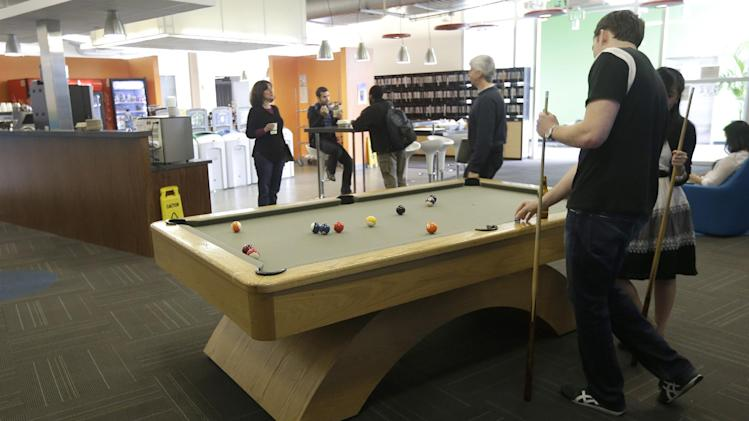 Google employees shoot pool at in a break room at the Google campus in Mountain View, Calif., Friday, March 15, 2013. Companies say extraordinary campuses are a necessity, to recruit and retain top talent, and to spark innovation and creativity in the workplace. And there are business benefits and financial results for companies that keep their workers happy. (AP Photo/Jeff Chiu)